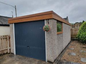 Refurbished Concrete Garage with Blue Garage Door